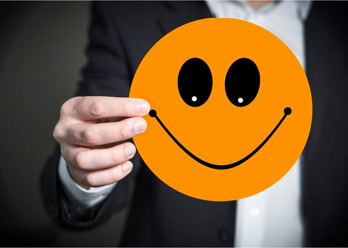 hombre sujetando un emoji sonriente de color naranja